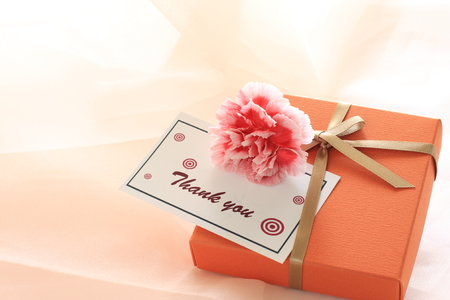 カーネーションを持つオレンジ色のギフト ボックス