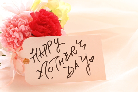 mothers day: artificial flower and hand written Mothers day greeting care Stock Photo