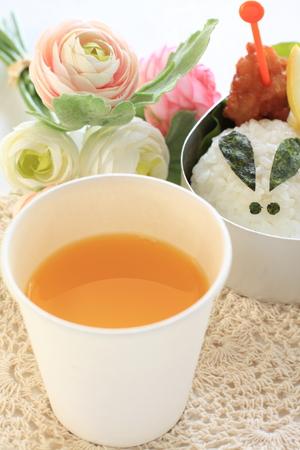 bento: paper cup of orange juicy with bento