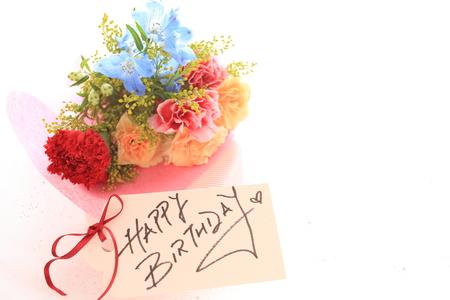 Mano de la tarjeta de cumpleaños escrita y ramo de flores Foto de archivo - 51117600