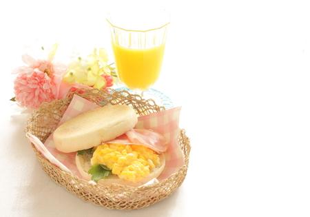 イングリッシュ ・ マフィンとジュースのスクランブル卵サンドイッチ