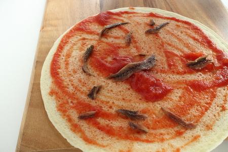 インスタントのピザ生地にトマトソース 写真素材