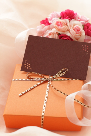 orange color gift box and artificial flower bouquet