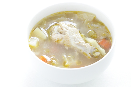 Chicken and vegetable soup isolated on white