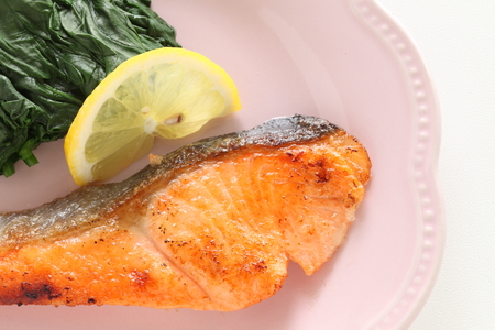 Salmon fillet sauteed served with lemon and spinach Stock Photo