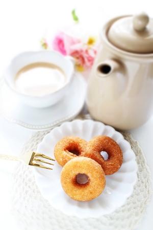 Donut de azúcar y té de leche con flor Foto de archivo - 97110882