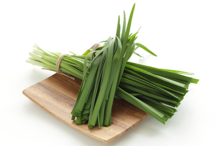 Chinese vegetable, leek on wooden plate Stockfoto