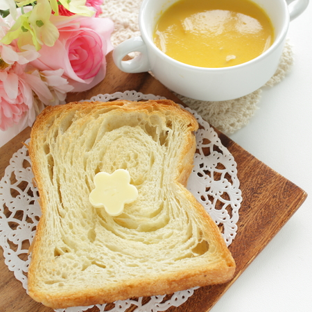 Sliced Danish bread with butter on wooden plate