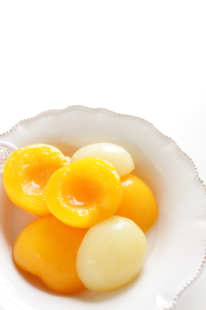 Canned fruit, yellow and white peach on bowl