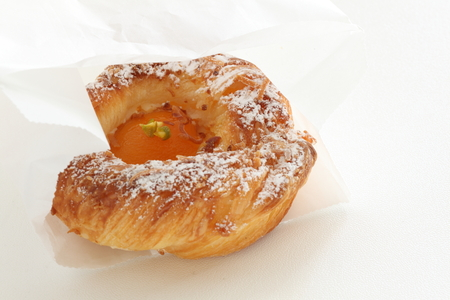 Apricot pasty bun in paper bag Stock Photo