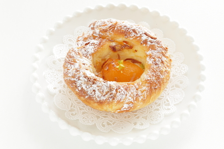 Apricot pasty bun on white dish with copy space