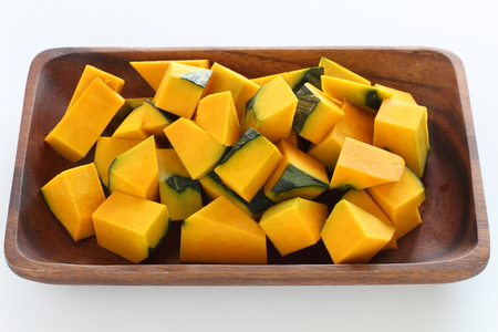 Chopped pumpkin on wooden plate