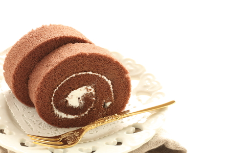 Homemade chocolate swiss roll on dish with fork
