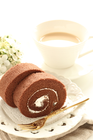 Homemade chocolate swiss roll on dish and milk tea Banque d'images