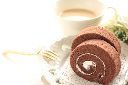 Homemade chocolate swiss roll on dish and milk tea Stok Fotoğraf