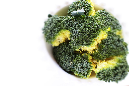 Chopped broccoli on whtie bowl with copy space