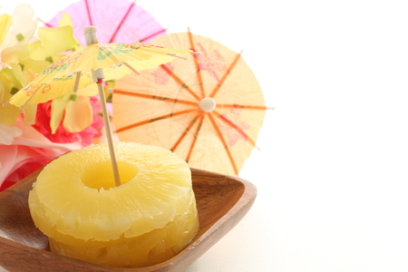 Canned fruit, pineapple and paper umbrella on tropical image