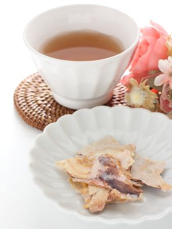 Tea and squid senbei on white