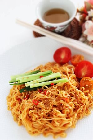 Asian spicy mixed noodles served with cherry tomato
