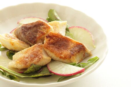 fried yellow tail fillet on radish and leaf vegetable