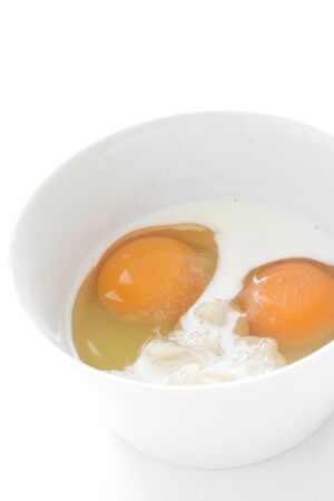 cream and raw egg in bowl with copy space
