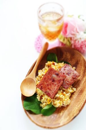 Luncheon meat and fried rice on wooden plate with copy space