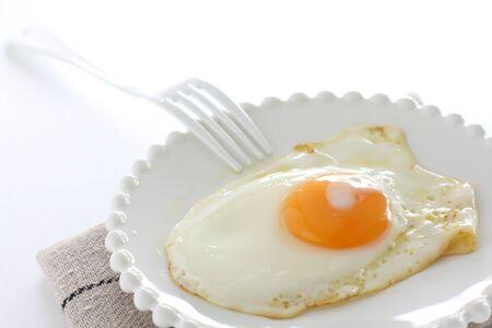 Sunny side up fried egg on white dish