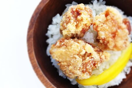 Asian food, fried chicken and rice in wooden bowl