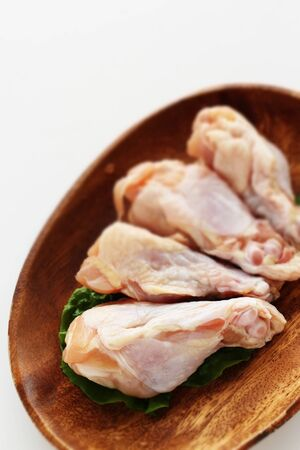 Chicken drumsticks on wooden plate with copy space Stock Photo