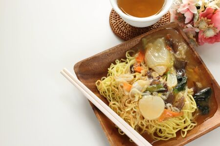 Chinese food, stir fried vegetarian and scallop on pan fried ramen noodles 写真素材