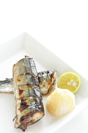 Japanese food, grilled pacific saury fish served with ground radish and lemon 写真素材