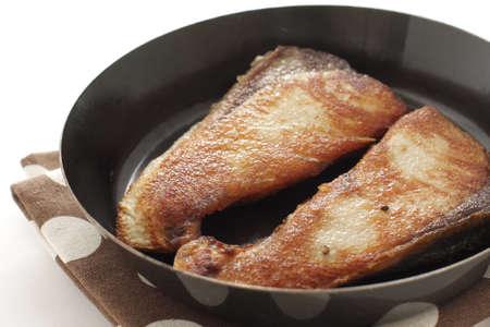Chinese food, pan fried yellow tail fish fillet in cooking pan