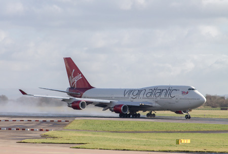 Manchester, United Kingdom - February 16, 2014  Virgin Atlantic Boeing 747 on runway, smoke rising from Asphalt, plane accelerating