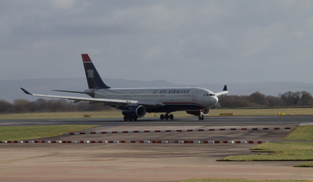 civilian: Manchester, United Kingdom - February 16, 2014  US Airways Airbus A330 accelerating on runway in Manchester Airport Editorial
