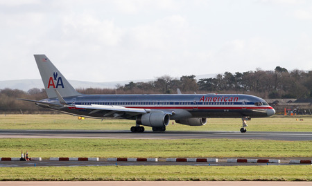emanating: Manchester, United Kingdom - February 16, 2014  American Airlines Boeing 767 plane taxiing after landing on Manchester Airport runway, heat emanating from engines