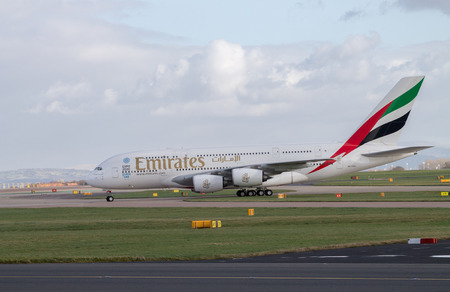 Manchester, United Kingdom - February 16, 2014  Emirates Airlines Airbus A380 arriving to Manchester Airport, side profile, clouds on background
