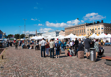 Tourists and locals shopping and sightseeing in Market Square, Central Helsinki, sunny weather