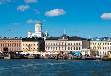 Iconic and beautiful Helsinki skyline featuring dome of Lutheran Cathedral, people sitting in cafeterias of Market Square, sunny weather with several clouds and blue sky