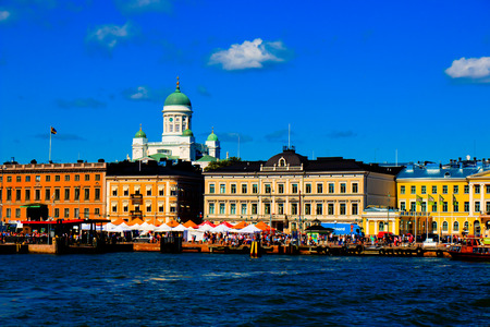 Iconic and beautiful Helsinki skyline featuring dome of Lutheran Cathedral, people sitting in cafeterias of Market Square, sunny weather with several clouds and blue sky, HDR