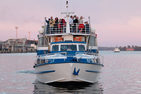 touristic: A ferry full of tourists arriving to Helsinki Harbour, dusk with a light cloud, tourists standing on top of the ferry, watching iconic Helsinki scenery Editorial