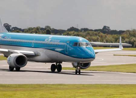 klm: KLM Cityhopper Embraer ERJ-190 PH-EZB passenger plane taxiing on Manchester International Airport runway.