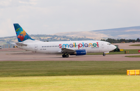 fly: Small Planet Airlines 737 charter passenger plane taxiing on Manchester International Airport tarmac. Editorial