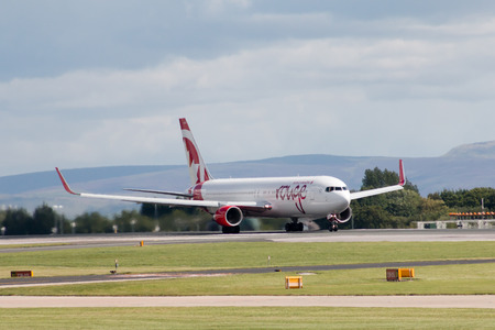 boeing: Air Canada Boeing 767-300ER passenger plane in Rouge colours, taking off from Manchester International Airport runway.