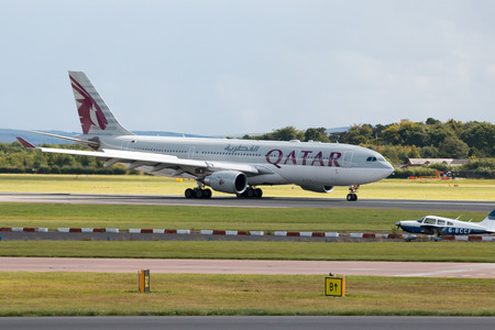 airways: Qatar Airways Airbus A330 wide-body passenger plane taxiing after landing to Manchester International Airport. Editorial