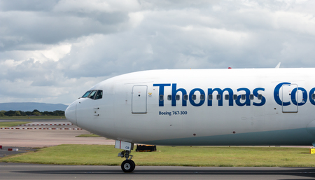 boeing: Thomas Cook Boeing 767 wide-body passenger plane taxiing on Manchester International Airport taxiway.