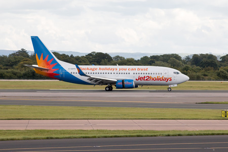 taking off: Jet2 Holidays Boeing 737 narrow-body passenger plane taking off from Manchester International Airport runway. Editorial