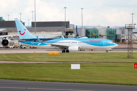 boeing: Thomson Airways Boeing 737 narrow-body passenger plane G-FDZU taxiing on Manchester International Airport taxiway.