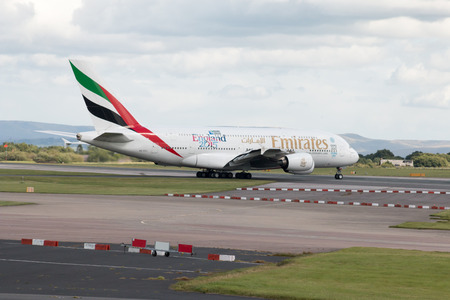 doubledecker: Emirates Airbus A380 double-decker wide-body passenger plane taxiing on Manchester International Airport taxiway.