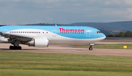 airways: Thomson Airways Boeing 767 wide-body passenger plane G-OBYH taxiing on Manchester International Airport taxiway.