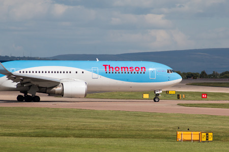 boeing: Thomson Airways Boeing 767 wide-body passenger plane G-OBYH taxiing on Manchester International Airport taxiway.